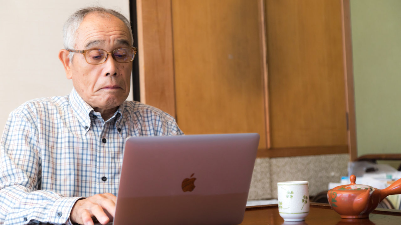 株価のチェックに余念がない高齢者の男性の画像